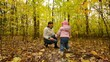 Little Baby is Playing with Mother in Autumn Colorful Forest