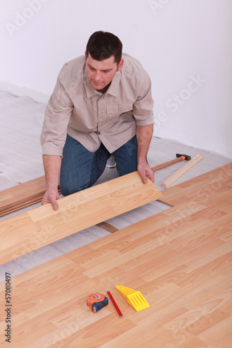 Labourer slotting together laminate flooring