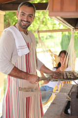 Man preparing kebabs on bbq