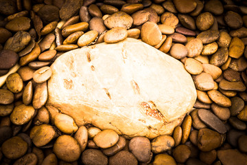 A big river stone on small river stone background