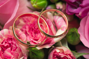 Gold wedding rings of the groom and the bride on a bunch of flow