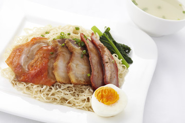 Chinese style egg noodle with roasted duck and pork,close-up