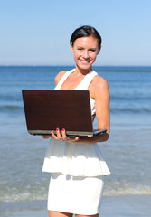 Attractive woman with notebook on the beach