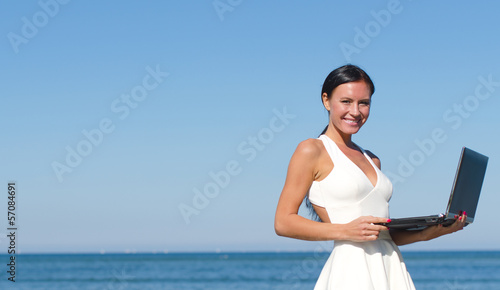 Attractive woman with notebook on the beach. Place for text