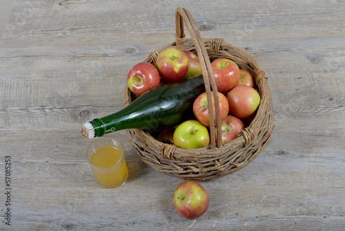 panier de pomme et bouteille  avec un verre de cidre