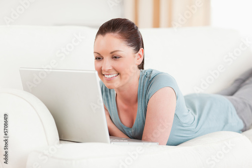 Attractive woman relaxing with her laptop while lying on a sofa