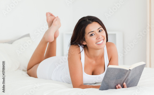 cute woman lying on bed with book looking into camera