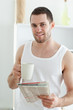Portrait of a smiling man drinking coffee while reading the news