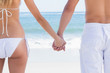 Young couple in swimwear holding hands