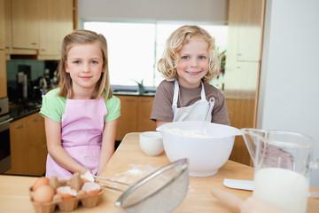 Smiling siblings preparing dough