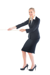 Cheerful blonde businesswoman pulling a rope