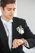 Handsome bridegroom watching the clock