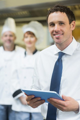 Young restaurant manager holding his tablet
