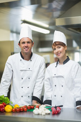 Two young chefs posing in a kitchen