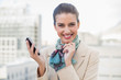Delighted smart brown haired businesswoman holding a mobile phon