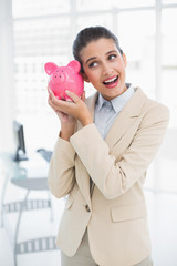Surprised smart brown haired businesswoman shaking a piggy bank