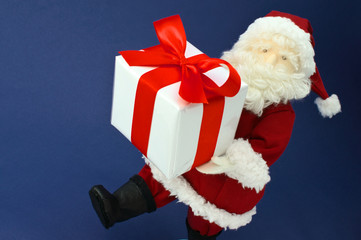 Cute stuffed toy Santa Claus hurrying with large Christmas prese