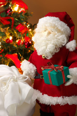 Cute stuffed toy Santa Claus giving a Christmas present.