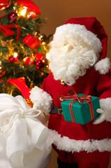 Cute stuffed toy Santa Claus giving a Christmas present.
