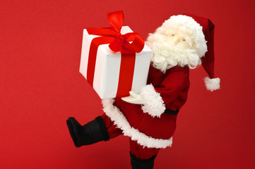 Cute stuffed toy Santa Claus carrying large Christmas present.