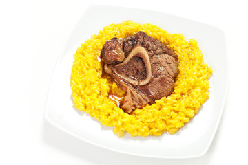 riso allo zafferano con ossobuco di bovino su sfondo bianco