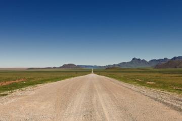 endlos gerade Schotterstraße in einer Wuestenlandschaft, Namibia