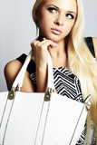 fashionable beautiful blond woman with white handbag. shopping