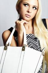 fashionable beautiful blond woman with white handbag. shopping