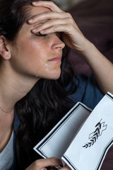 Crying young woman holding obituary