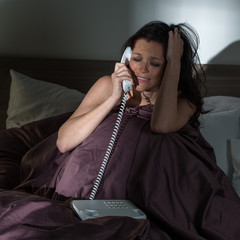 Crying woman calling phone in bed