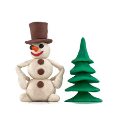 plasticine snowman standing near the Christmas tree