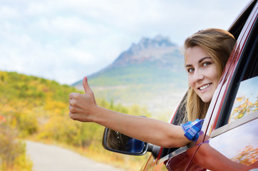 Happy driver woman shows thumb up
