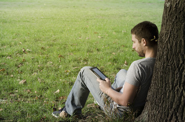 .Young man reading e-book