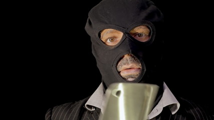 Masked criminal rising from darkness with chopper knife
