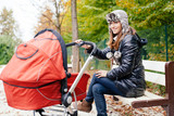 Young woman sitting on park bench with baby in stroller