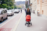 Young woman pushing her baby in stroller on the street