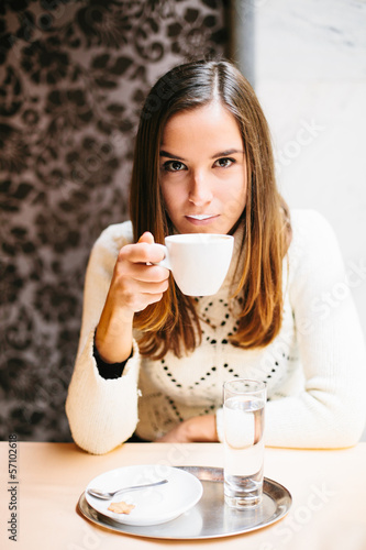 Young woman drinking cappuccino in cafe