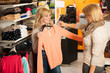 Womans shopping - Two girls in a clothes shop choosing garment