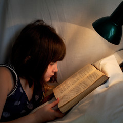 girl read book on bed at night