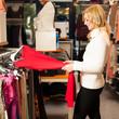 Young woman choosing a garment in a  shop
