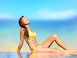 Sunbathing woman relaxing under sun in luxury spa