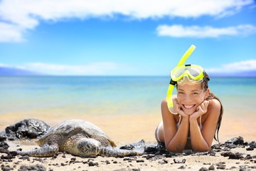 Beach travel woman on Hawaii with sea sea turtle