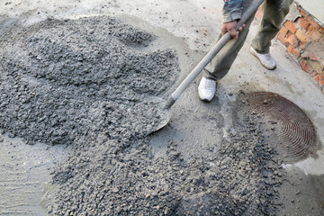 Hand mixing concrete worker with shovel at construction site