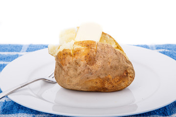 Baked Potato on White Plate and Blue Towel with Butter