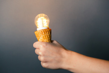 hand holding led lamp in ice cream cone, innovation concept