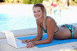 Woman laying poolside with laptop