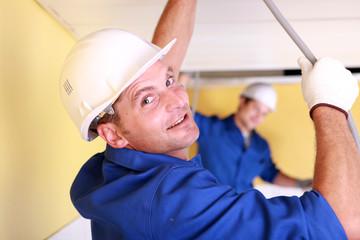 Two plumbers repairing ceiling