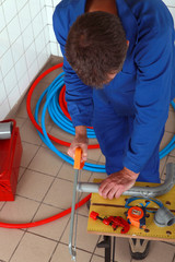 Man sawing tube seen from above