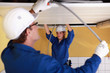 Two electricians working on the ceiling
