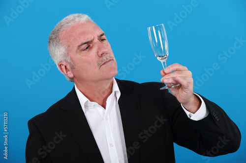 Man looking at a wine glass